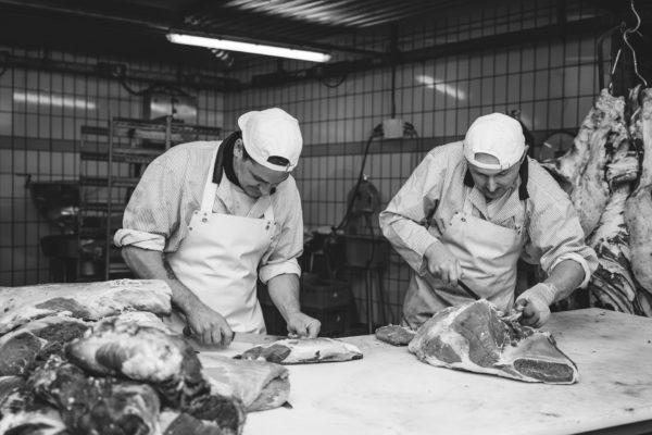 Il mastro macellaio che prepara i prosciutti, la macelleria Bernardi a Brunico
