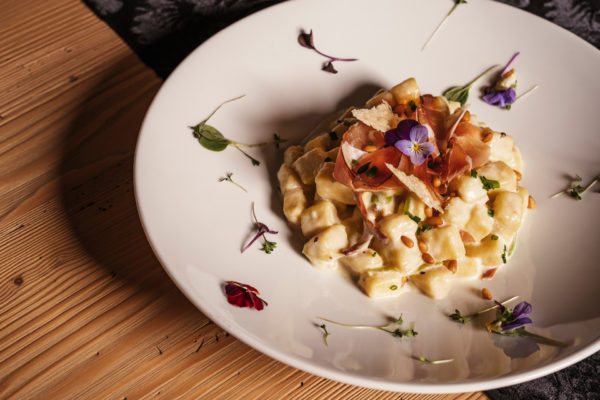 Gnocchi alla crema con Speck Bernardi affumicata e un condimento di pinoli ed erbe selvatiche dell'Enotheque Bruneck